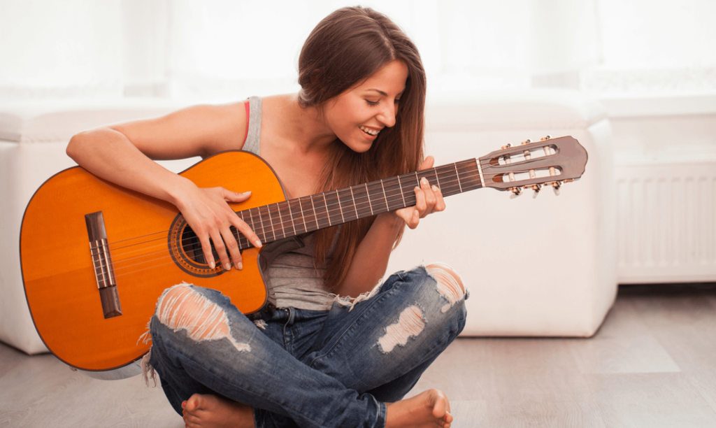 woman smiling while playing the guitar
