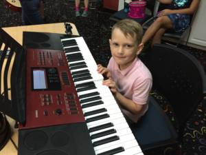 happy student taking piano classes in Miami